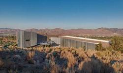 An architecturally stunning home by renowned architect Will Bruder. Nestled into the mountain on 6.58 acres the homes unique design is well suited to Nevada terrain and climate. A low maintenance home of concrete and glass with high ceilings, low voltage